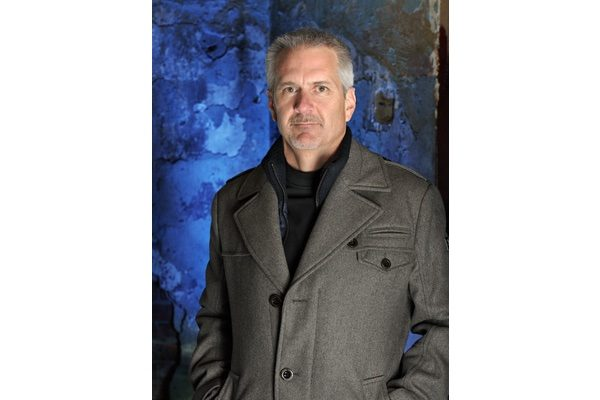 Author headshot of a man in a jacket