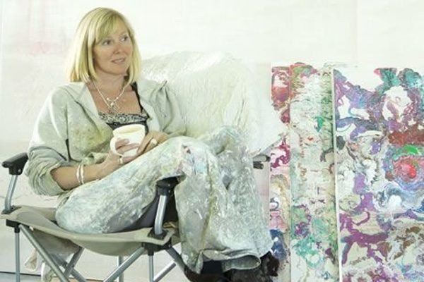 A woman sitting in a folding chair next to colorful oil paintings