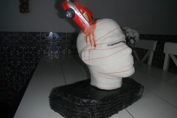 An image of a casted head with a toy car running into it