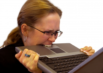 Image of a woman biting her laptop