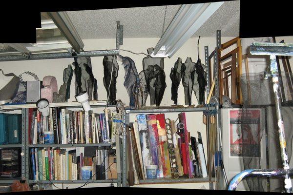 Donald Kolberg's studio, with mesh sculptures, materials, and art books