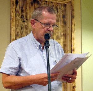 Poet activist Reuben Woolley reads poetry at a microphone.