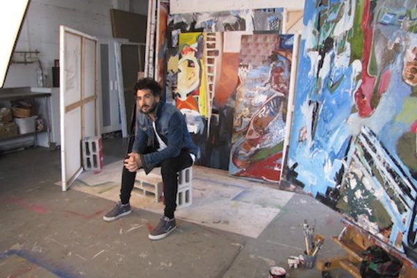 Gil Desiano Bitton in front of his paintings