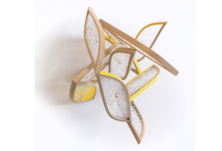 A wooden and glass abstract sculpture with certain portions painted yellow