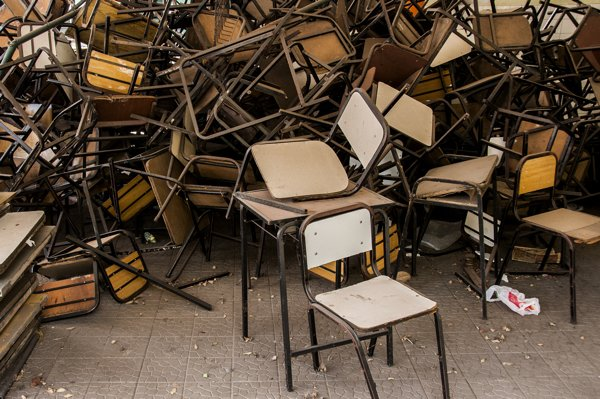 A photograph of a large number of school chairs haphazardly stacked on each other