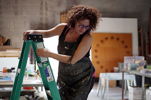 An artist looks down at her work from a ladder
