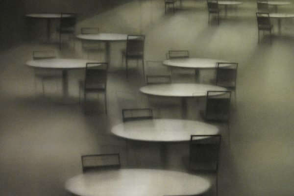 A painting of a number of empty tables shrouded in fog