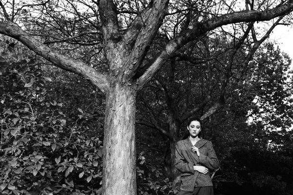 A black and white photograph of a woman standing beside a tall tree