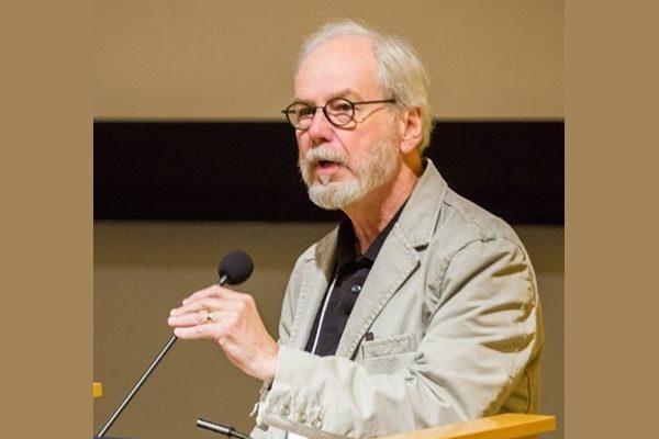 Writer Richard Hoffman stands at a podium giving a speech