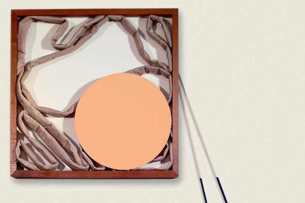 A collage of a circle and fabric in a wooden frame on a pale background
