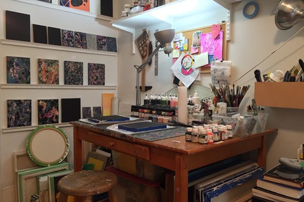A collage artists studio, with paint bottles lining the desk and art on the walls
