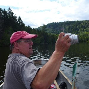 Artist Alan Bray canoes on a lake, taking photographs