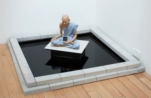 An installation of a buddha sitting in a black pool