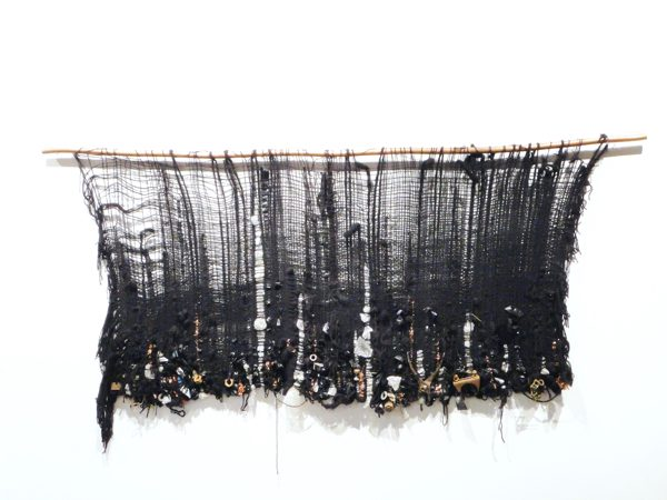 A black wall weaving with object woven into the bottom of the piece
