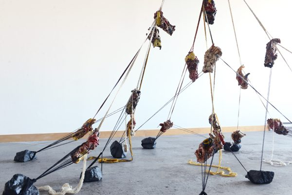 An installation of cords suspended from the ceiling, with cast hands climbing up the cords