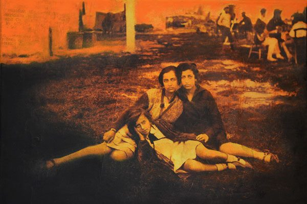A red-toned photograph of a group of three girls posing together
