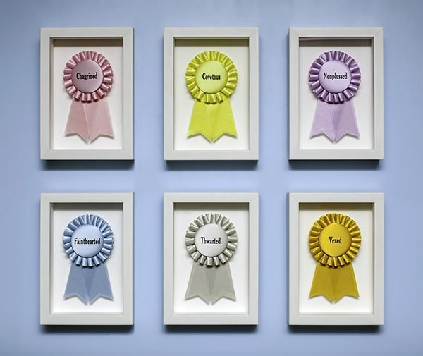 6 custom printed ribbons listing personality flaws that impede winning, framed in shadow boxes