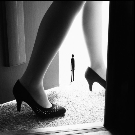 A close up photograph of a woman's feet walking through a doorway, with a small figure in between her calves