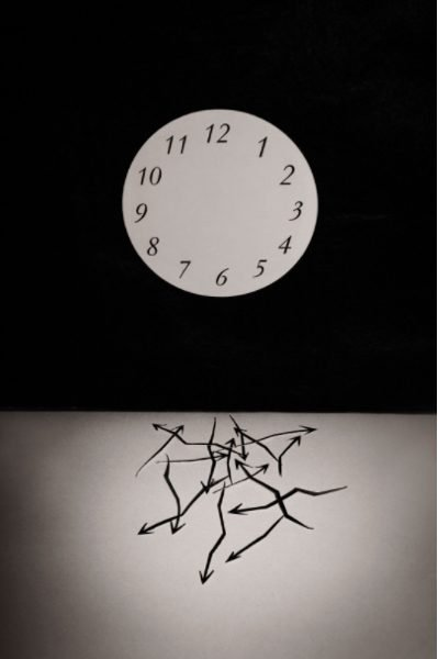 A photograph of an armless clock, with the arms at the bottom of the photograph in a tangle