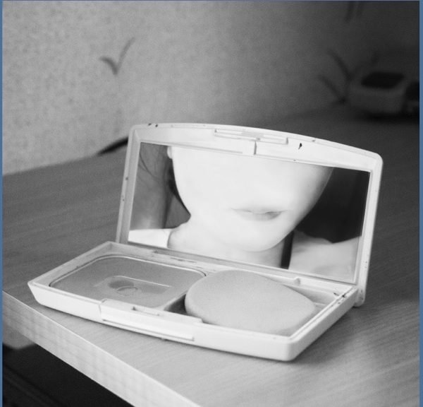A black-and-white photograph of a woman looking into the mirror of a makeup compact