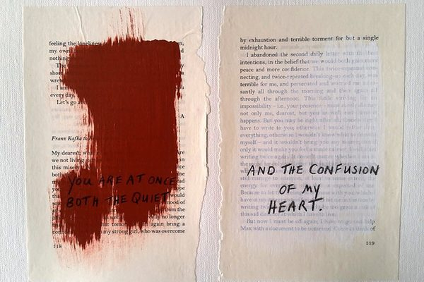 Ripped pages from a book with paint over the text, and new text written over