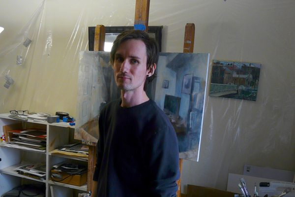 Painter Dillon Samuelson stands in his studio in front of his paintings