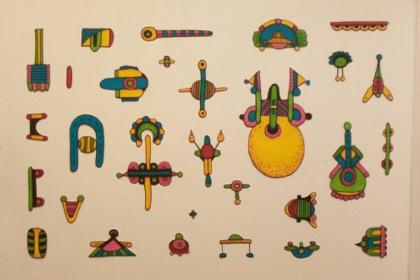 A collection of colorful textile figures arranged on a wall