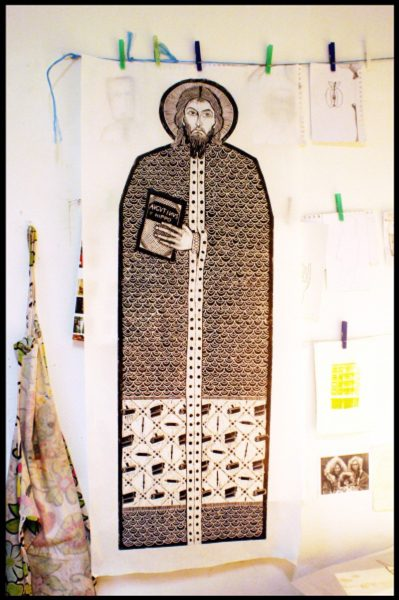 A large print of a drawing of the patron saint of printmakers, holding a text