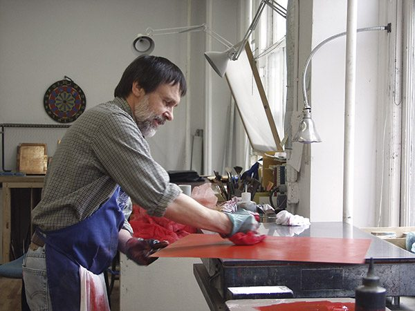 An artist inking a plate in his studio