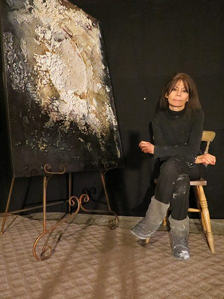 Painter Josie Bell sits next to one of her earthy abstract paintings