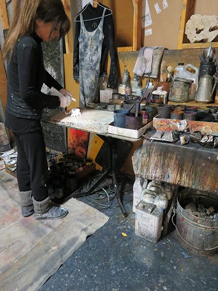 Josie Bell portions out paint for a work in progress in her artist studio