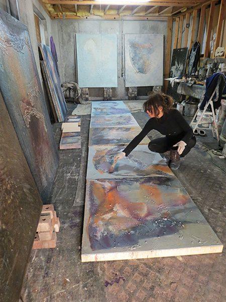 Josie Bell applies an oil glaze to her paintings on the floor of her studio
