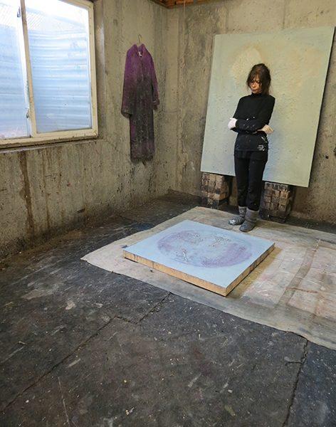 Josie Bell studies a work in progress on the floor of her studio