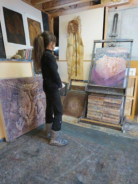 Josie Bell studies a painting in progress in her studio