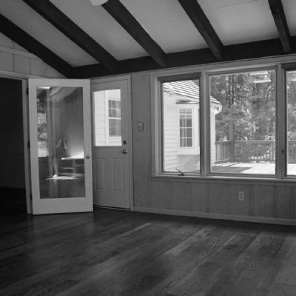 A photograph of an empty room, with the photographer's reflection in the glass pane of the door