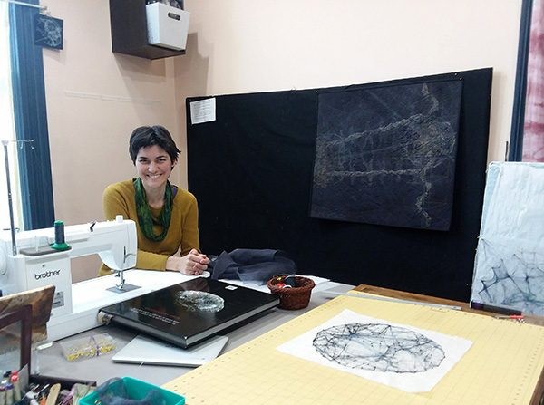 Quilting artist Shea Wilkinson in her studio with her sewing machine and works