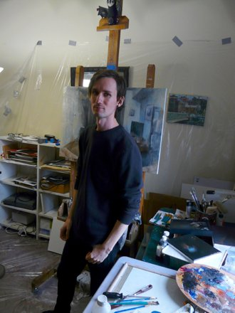 Painter Dillon Samuelson stands in his studio in front of his work