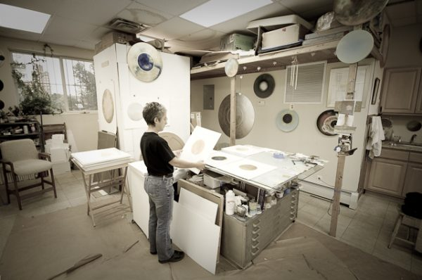 A sepia-toned photograph of an artist working in her studio