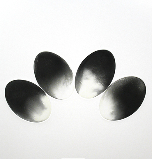 A black and white monotype of four ovals in an arc shape