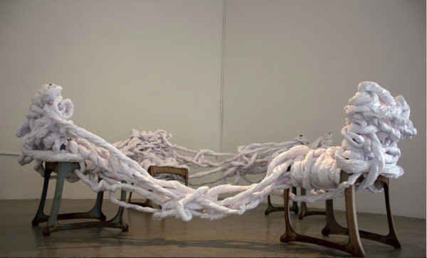 An installation of twisted and woven medical exam papers wrapped around chairs