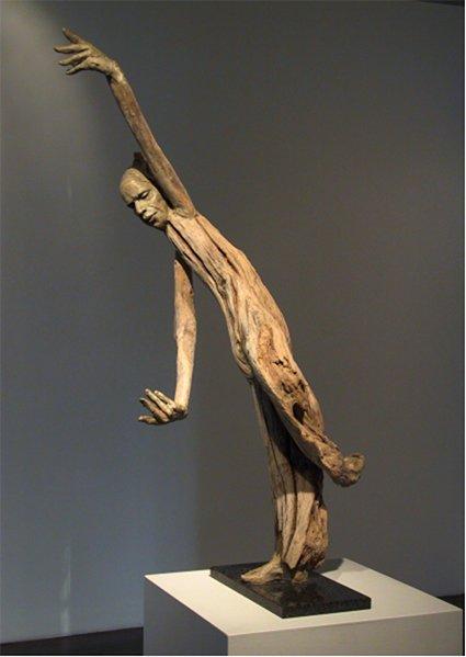 A sculpture of a human figure made from driftwood