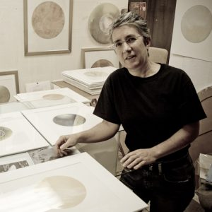 A sepia toned picture of an artist in her studio