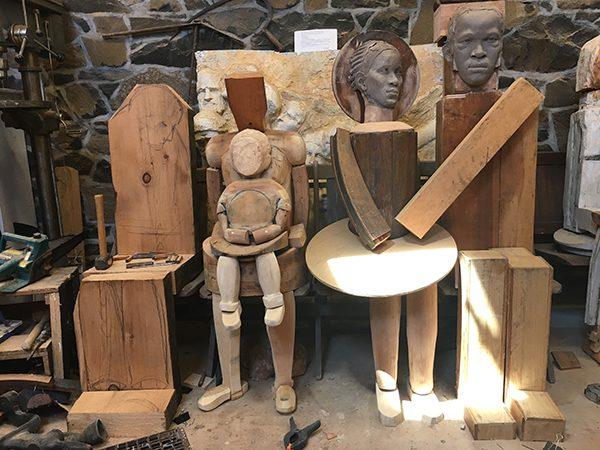 Wooden dolls and sculptures sit in Susan Clinard's studio