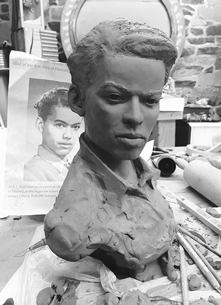 A black and white photo of a clay bust sculpture in process