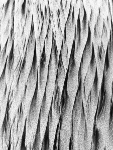 A closeup, black and white picture of sand resembling pointed lines