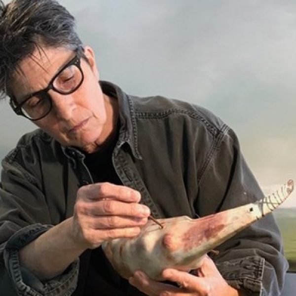 An artist works on a sculpture incorporating a found shell