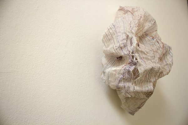 A paper and thread installation hangs on a gallery wall