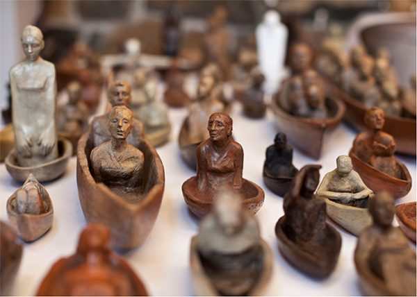 Small, terra-cotta boats carry people of various ages with different facial expressions.
