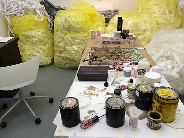 Weaving materials and paint scattered around an artist's studio