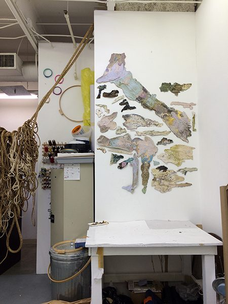 Painted plaster hung on the wall of an artist's studio